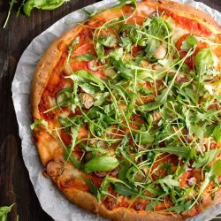 Pizza z mozzarellą, pomidorami i rukolą